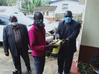 General Secretary Wlater Andhoga distributes food items to church members of Gatwekera as FPFK Kawangaware's Bishop Silas Mbambu looks on.